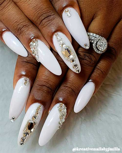 Cute white almond nails for dark skin hands adorned with some rhinestones