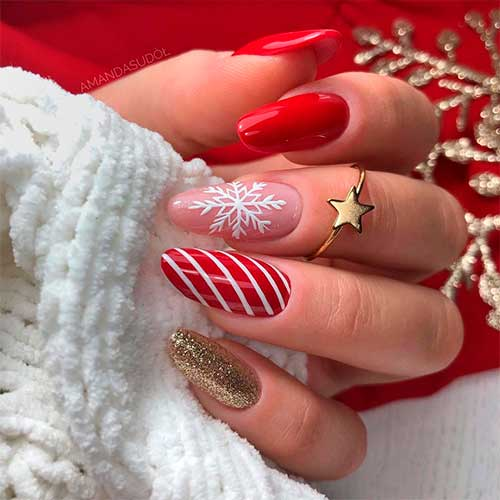 Cute red Christmas nails 2020 almond shaped with three accent white snowflake, candy cane, and gold glitter nails!